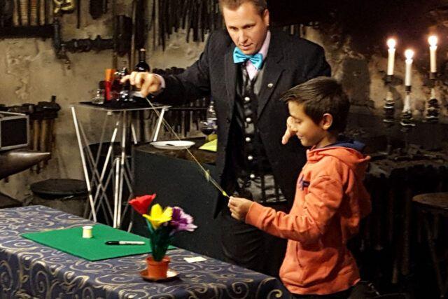Roger Zeller zeigt einem Kind einen Zaubertrick