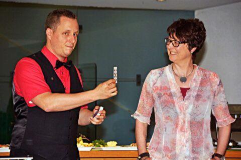 Roger Zeller zeigt einer Helferin aus dem Publikum eine Spielkarte