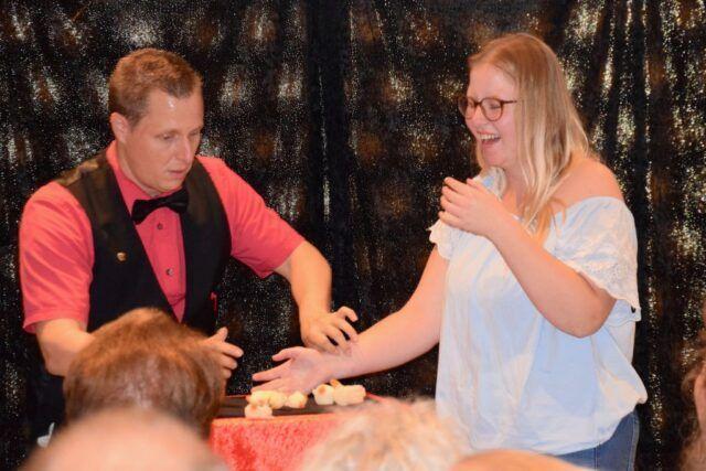 Roger Zeller zeigt erstaunter Helferin aus dem Publikum einen Zaubertrick