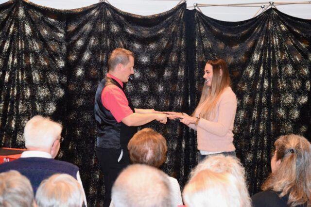 Roger Zeller zeigt mit Helferin aus dem Publikum einen Zaubertrick
