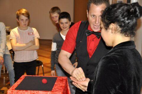 Roger Zeller zeigt Kindern verschiedene Zaubertricks