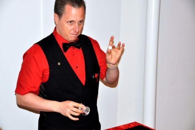 Roger Zeller zeigt einen Zaubertrick mit einer Kugel und einem Becher