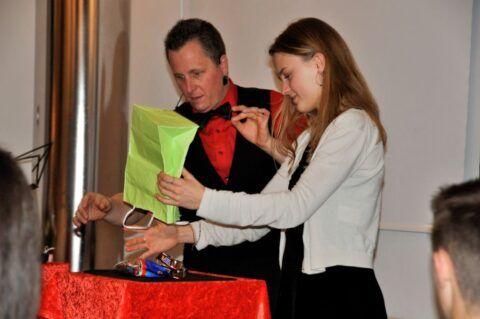 Roger Zeller zeigt einer Zuschauerin einen Trick